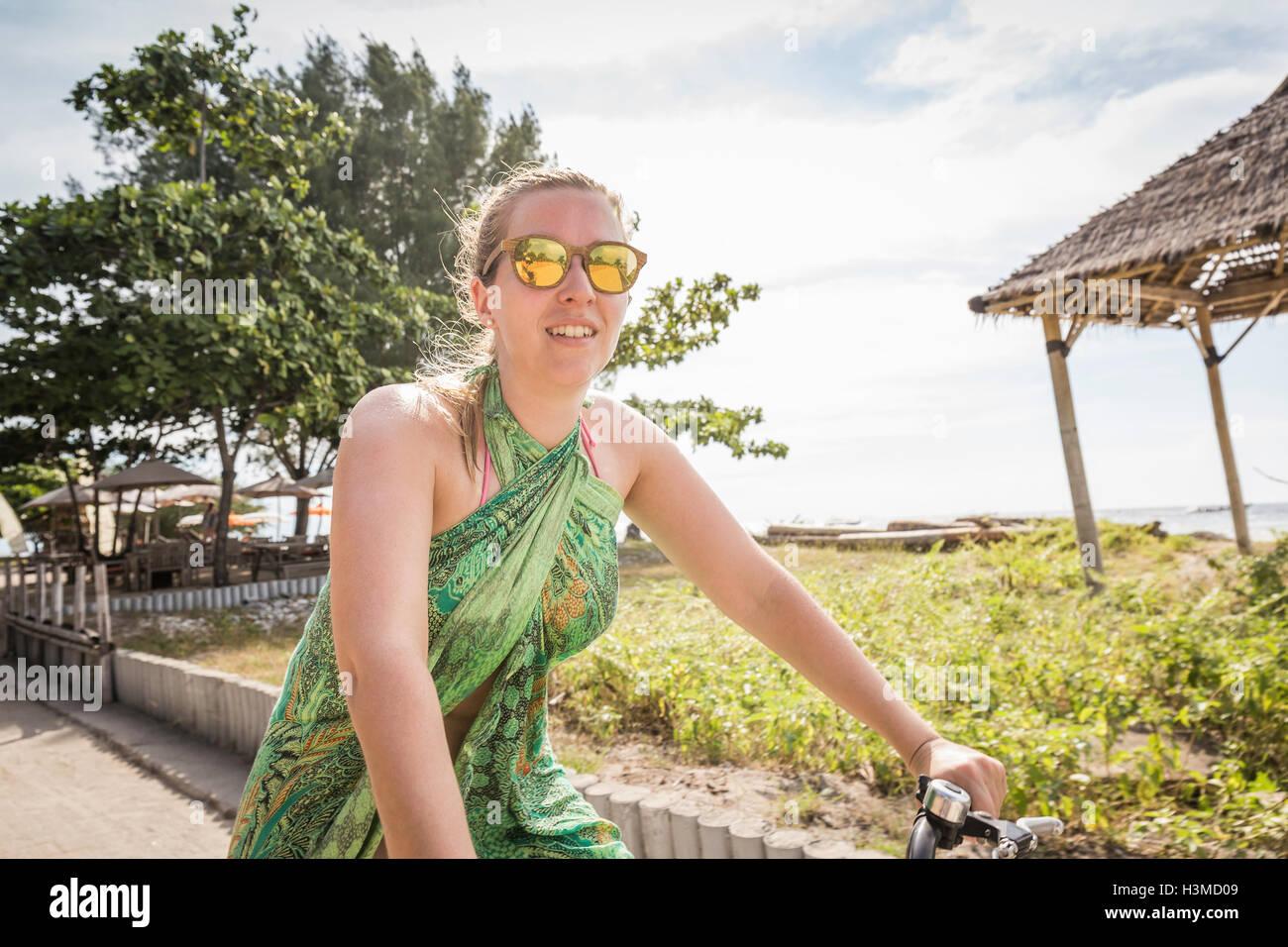 Woman cycling near coast, Gili Trawangan, Lombok, Indonesia - Stock Image