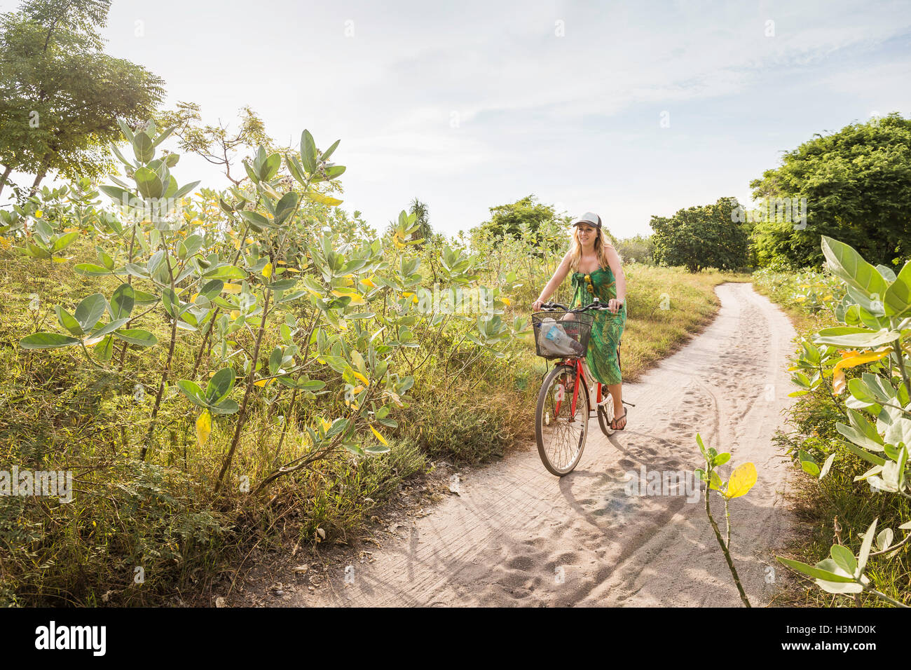 Young woman cycling on dirt track, Gili Meno, Lombok, Indonesia - Stock Image