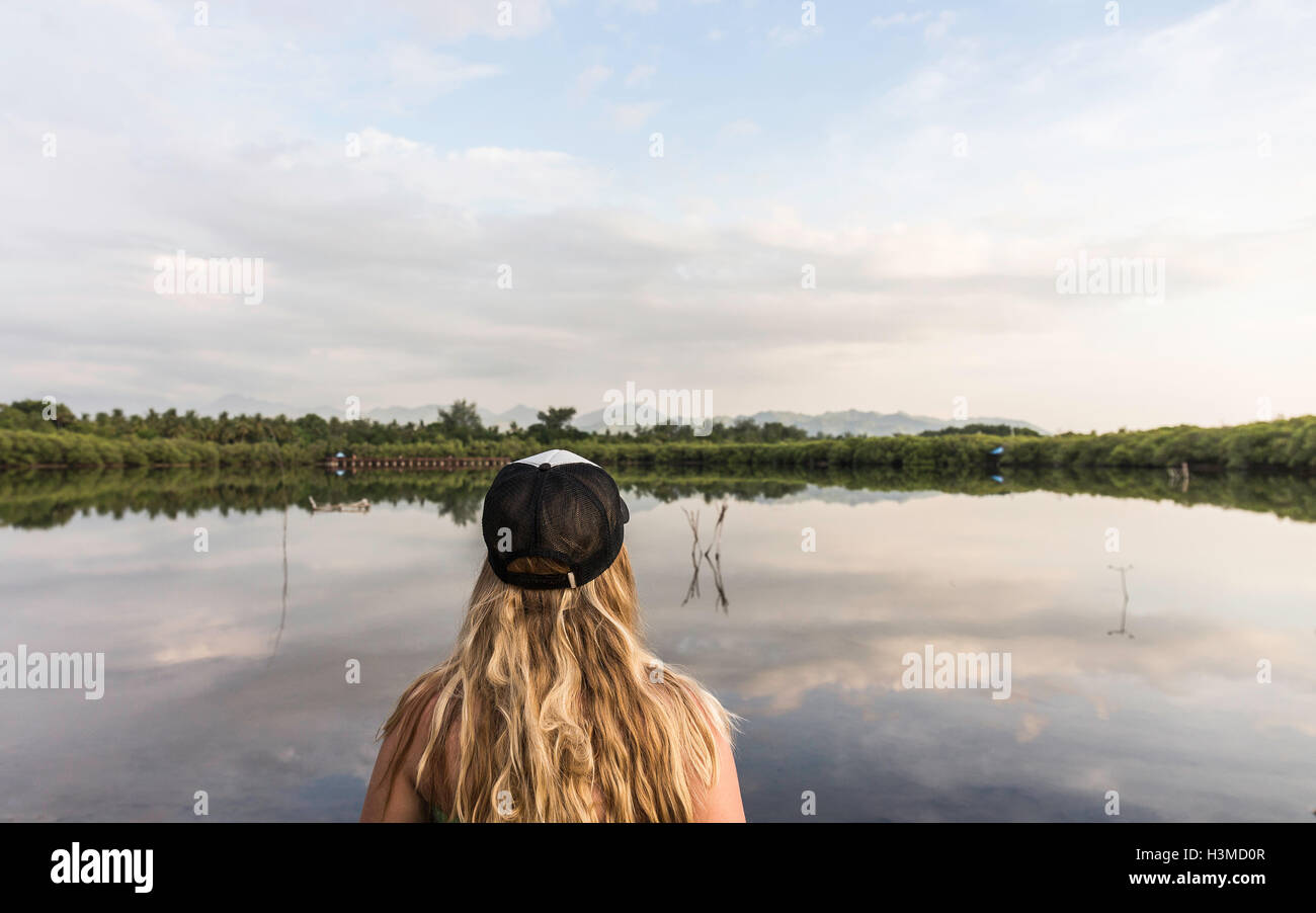 Rear view of young woman looking out over lake, Gili Meno, Lombok, Indonesia Stock Photo
