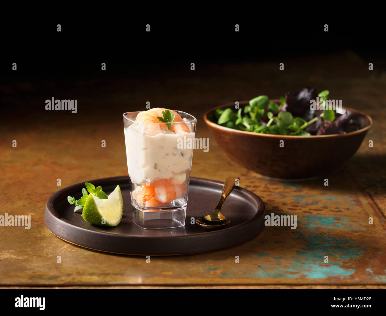 Christmas, celebration food, prawn and salmon appetiser, fresh slice of lime, thyme, salad leaves in bowl - Stock Image