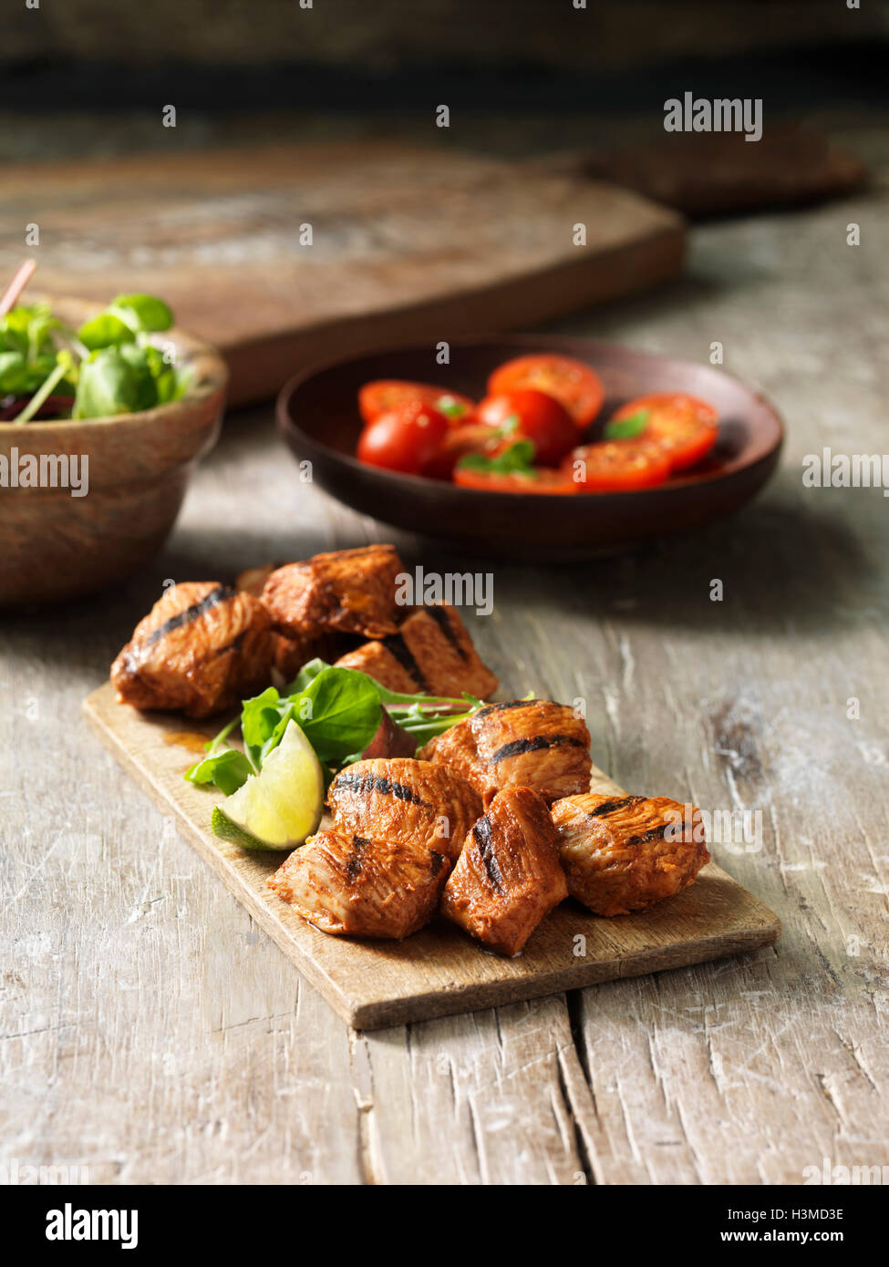 Hickory smoked bbq chicken, cherry tomatoes, fresh lime slice, green herbs - Stock Image