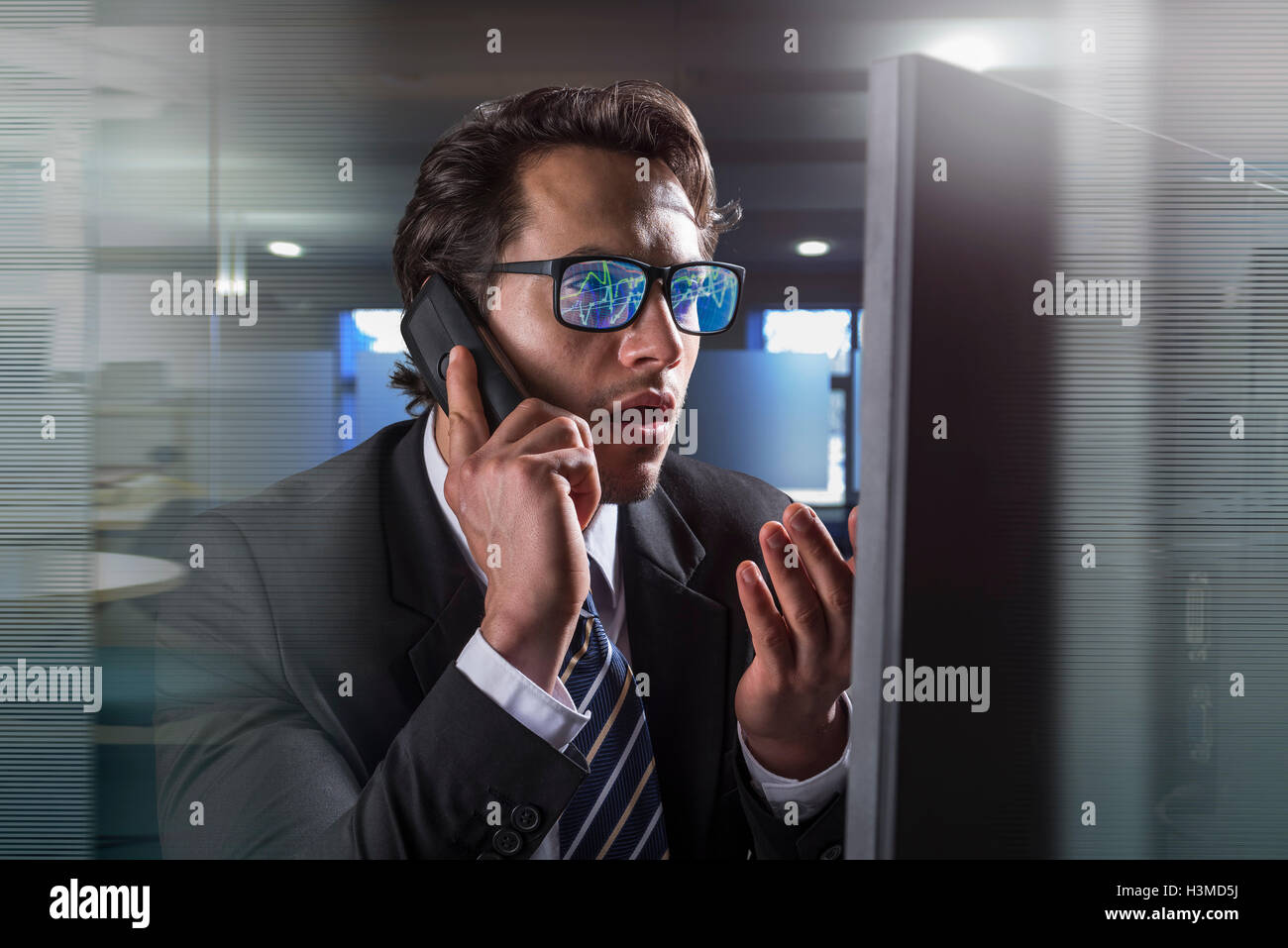 Composite image of businessman on phone at computer screen with graphical data reflected in glasses - Stock Image