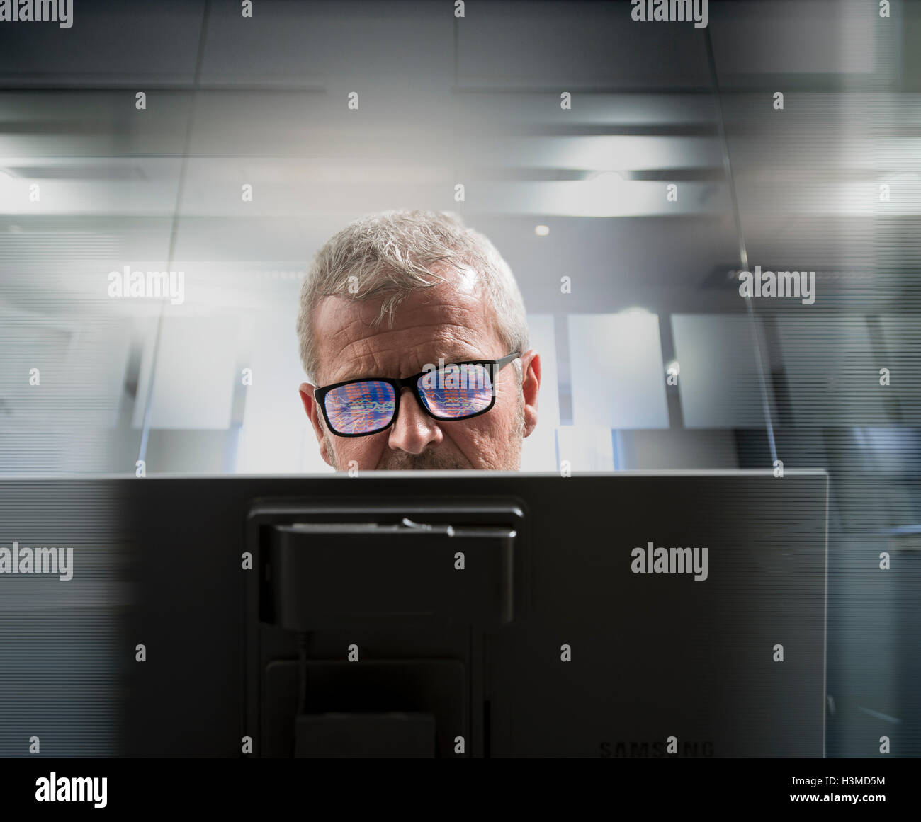 Composite image of businessman at computer screen with graphical data reflected in glasses - Stock Image
