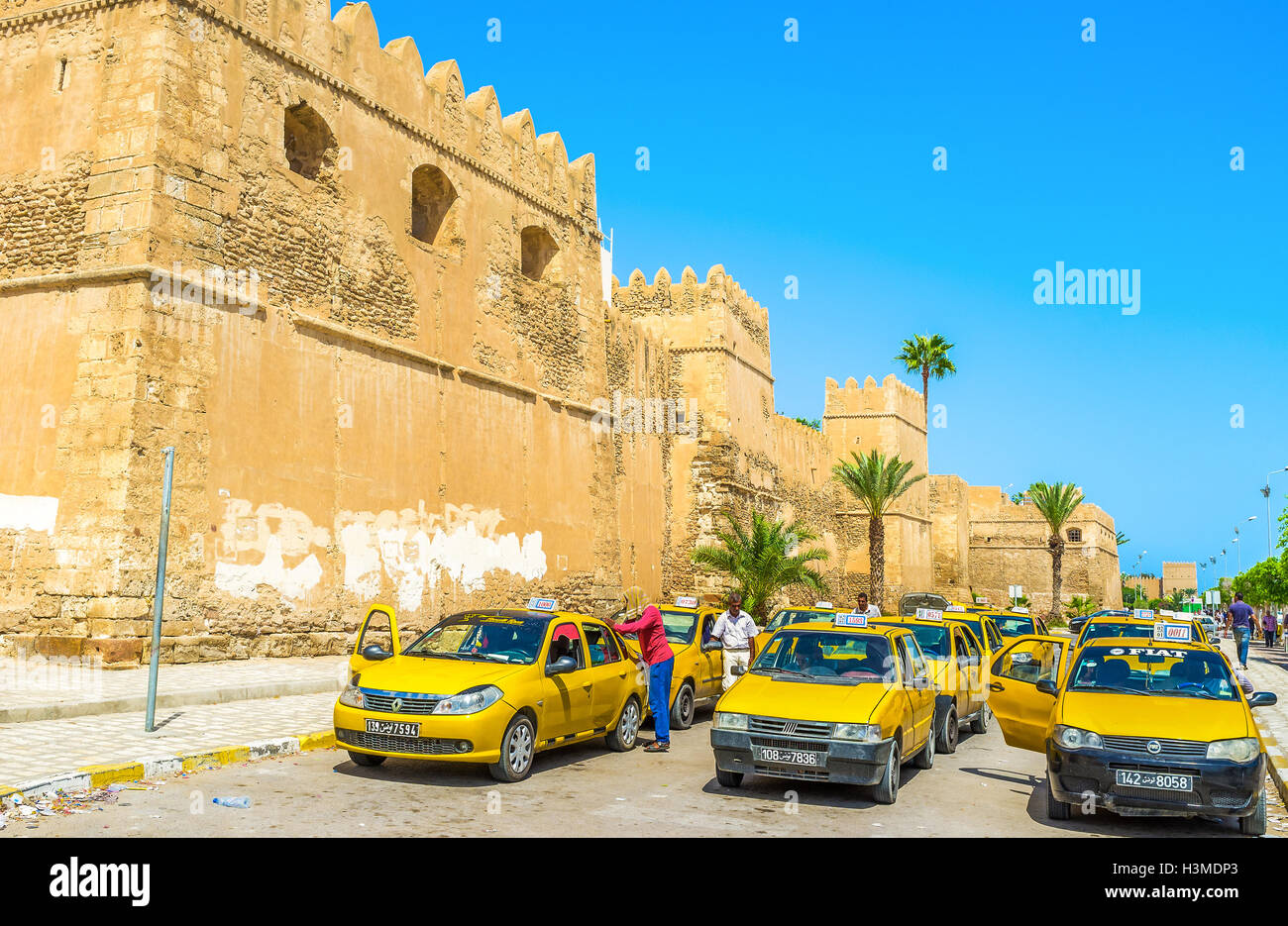The large taxi stand next to the Bab El Kasbah Gates, the drivers clean their cars and wait for the clients in Sfax. - Stock Image