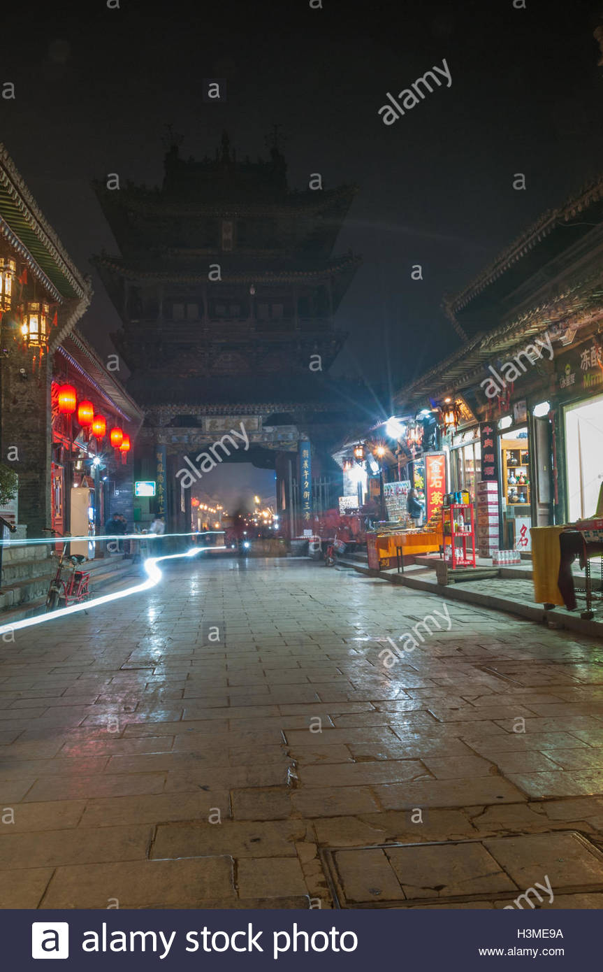 A light trail left by an ebike zipping through the cobbled South Street of Pingyao and under the City Tower building. - Stock Image