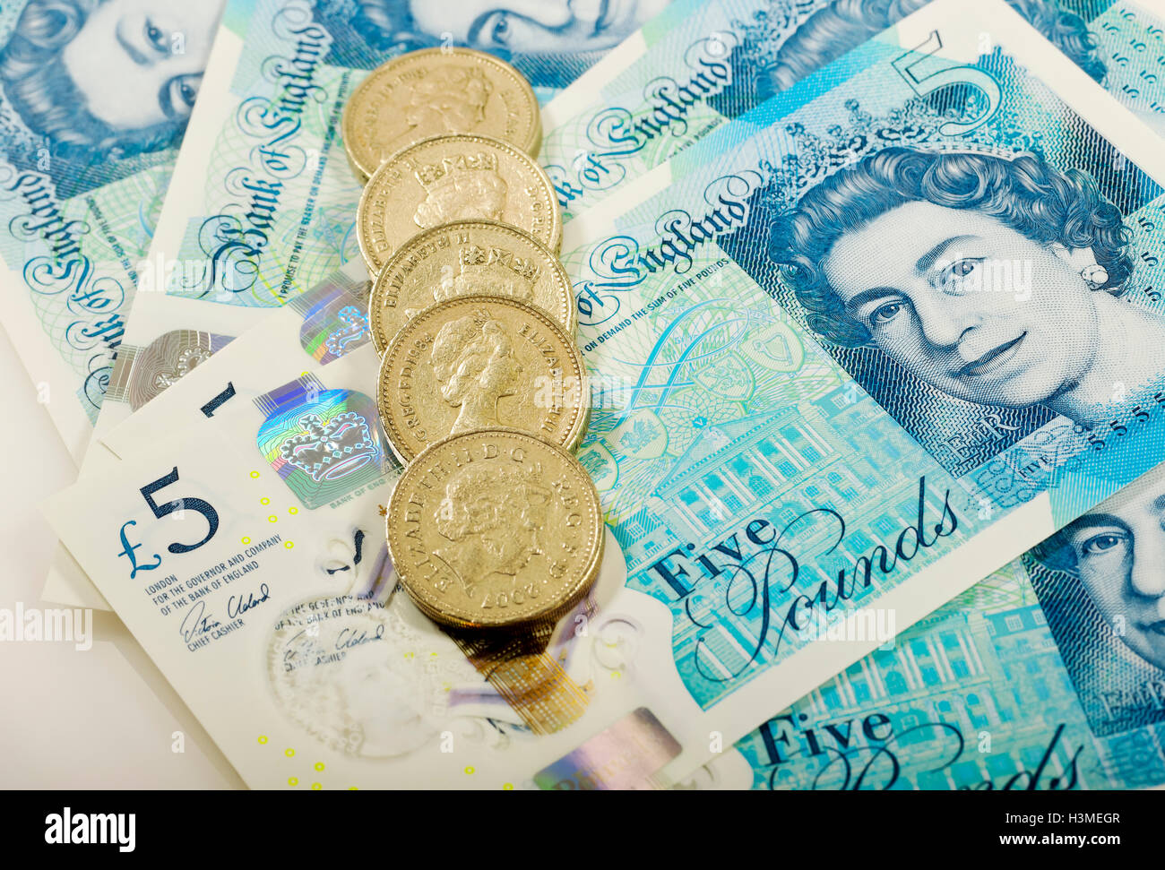 New polymer five pound notes and pound coins England UK United Kingdom GB Great Britain - Stock Image