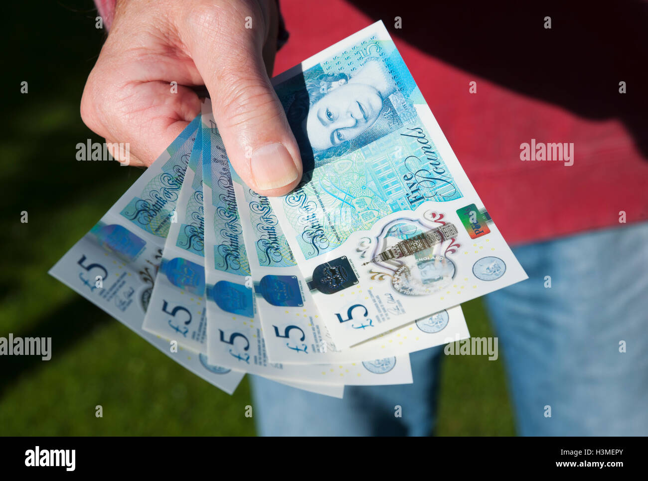 Man holding new polymer five pound notes England UK United Kingdom GB Great Britain - Stock Image