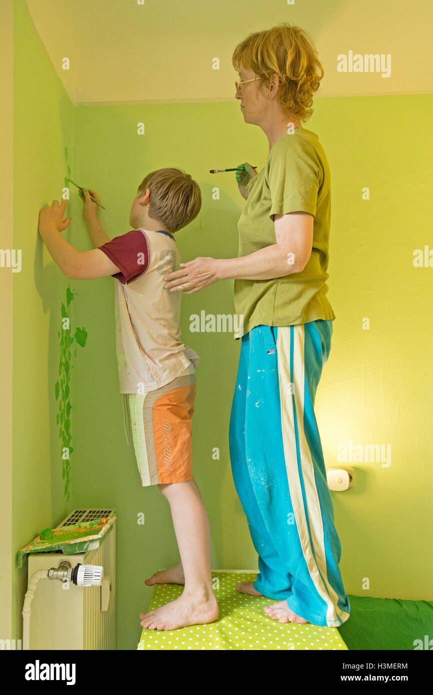 mother and son painting the flat - Stock Image