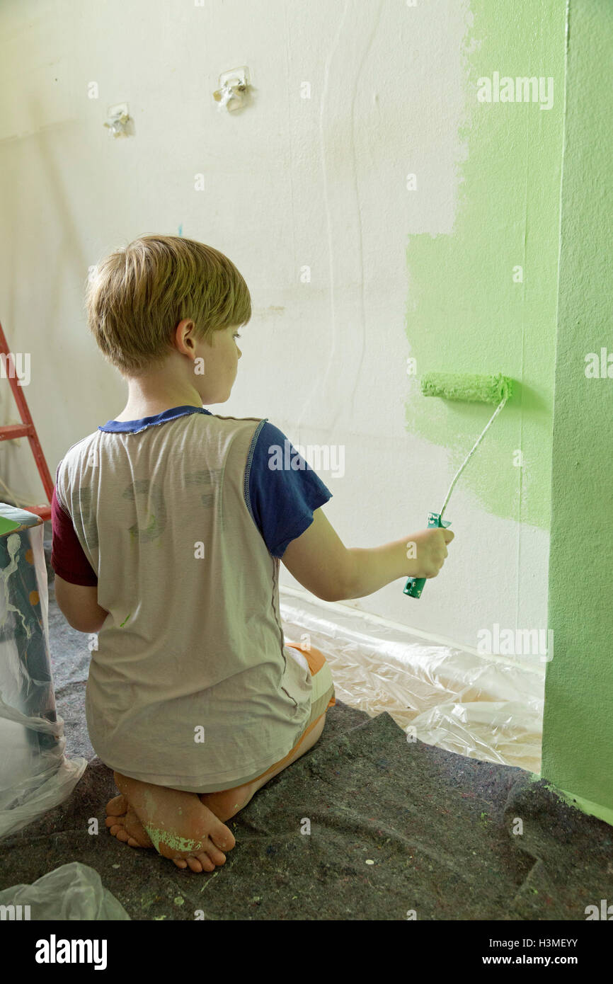 young boy helping to paint the flat - Stock Image