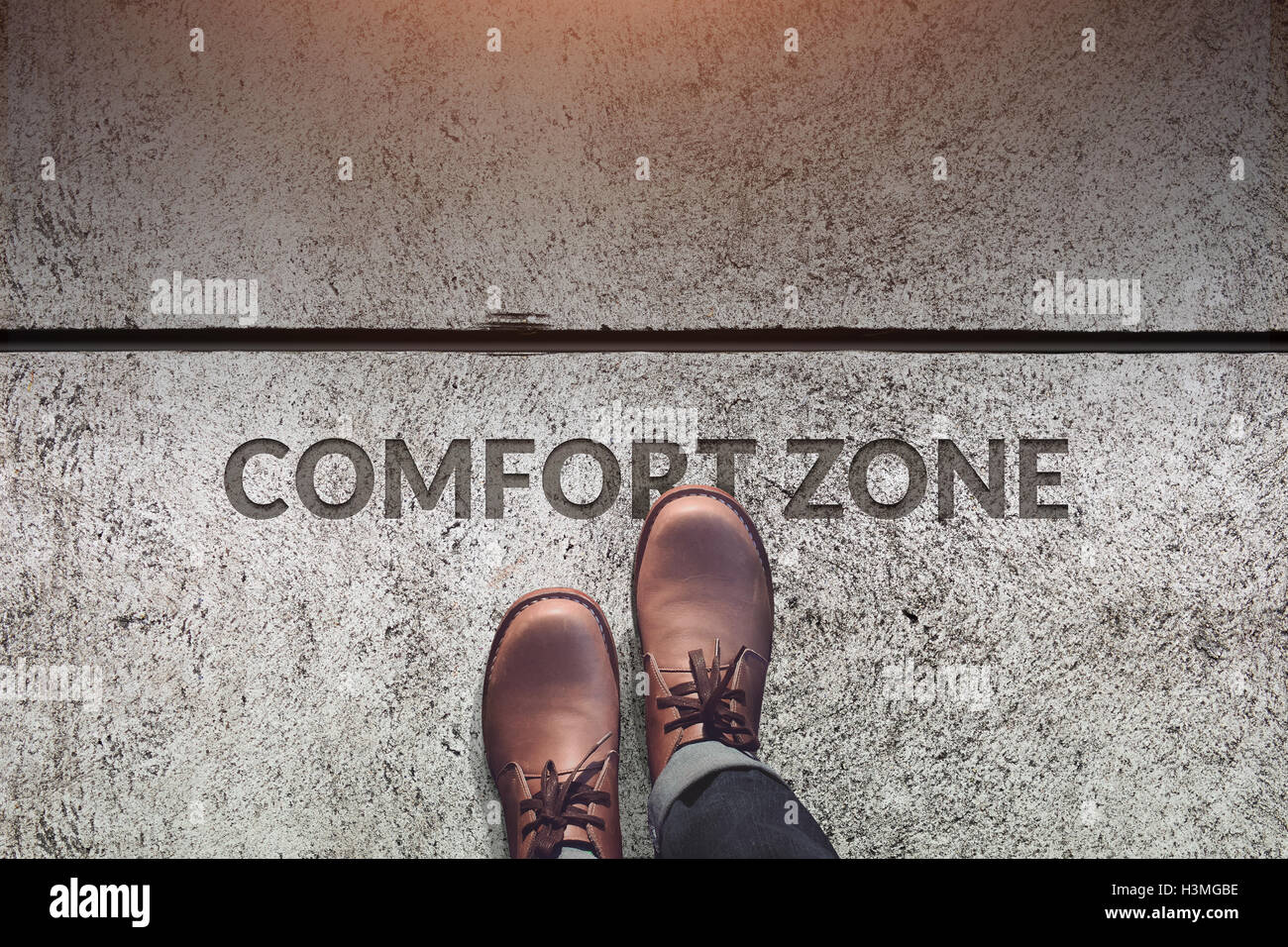 Comfort Zone Concept, Male with Leather Shoes Steps over a word : Comfort Zone with line on Concrete Floor, Top view Stock Photo