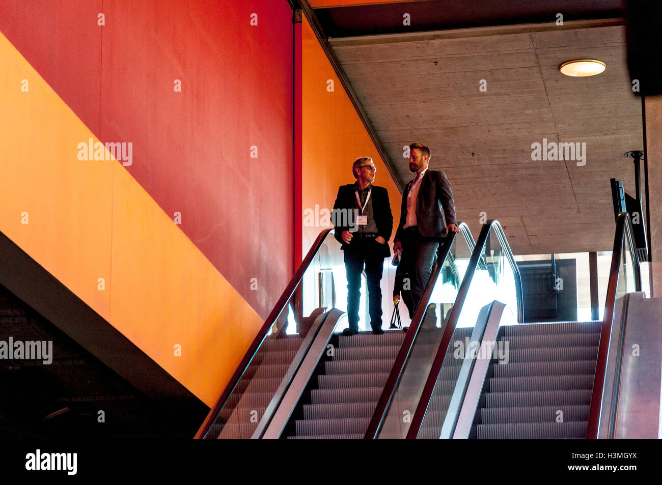 Business conference attendees on an esculator at the conference centre in St.Gallen, Switzerland - Stock Image