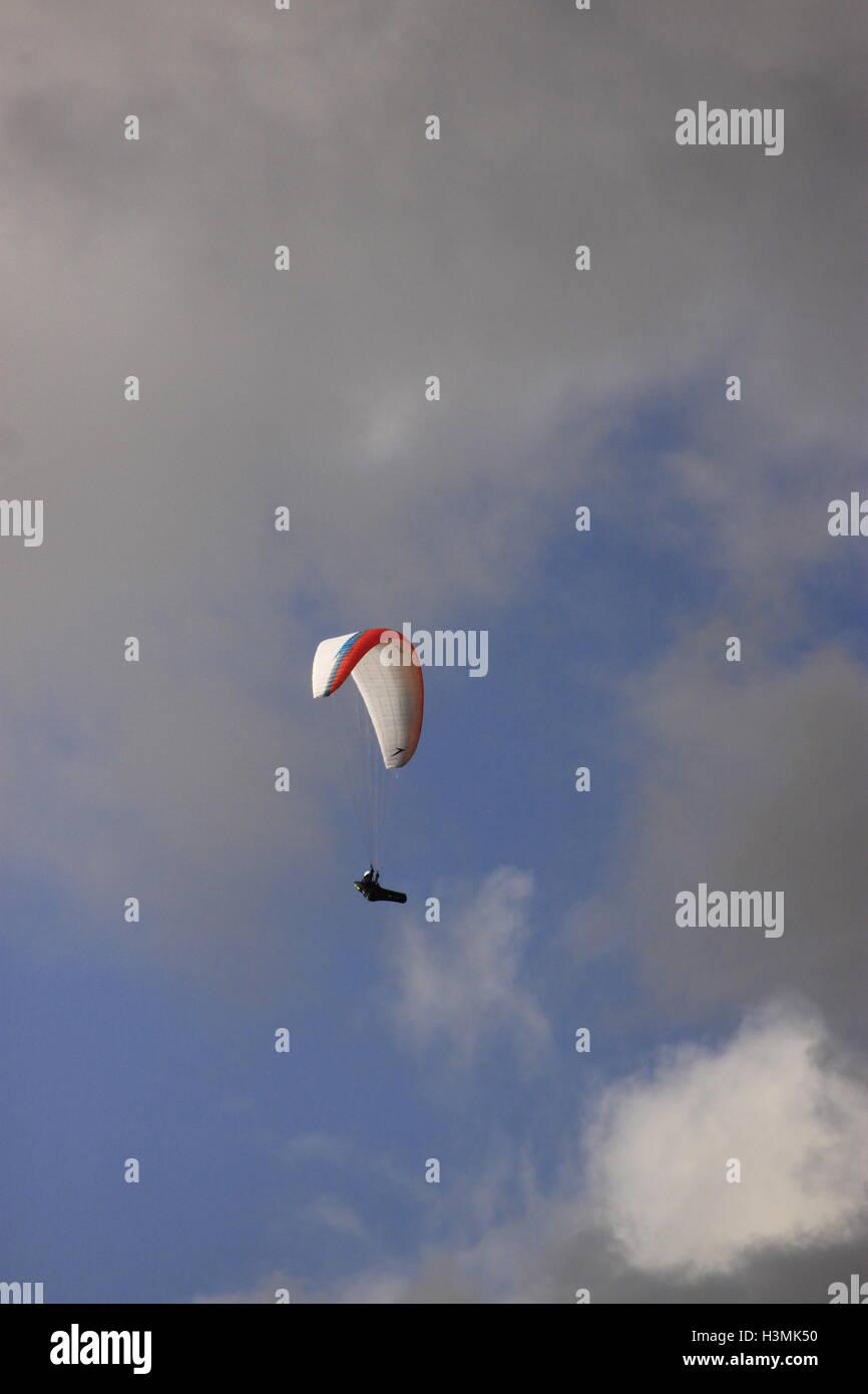 Paraglider descending flight through cloudy sky outdoor pursuits Mam Tor, Castleton, Peak District, Derbyshire, - Stock Image