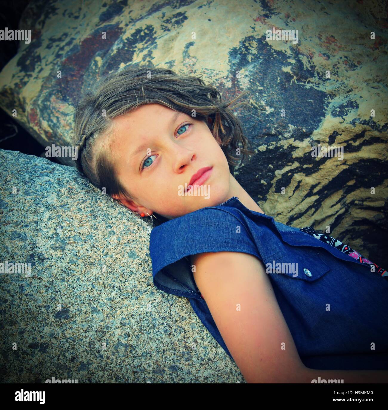 young blue eyed female model posing on colorful boulders