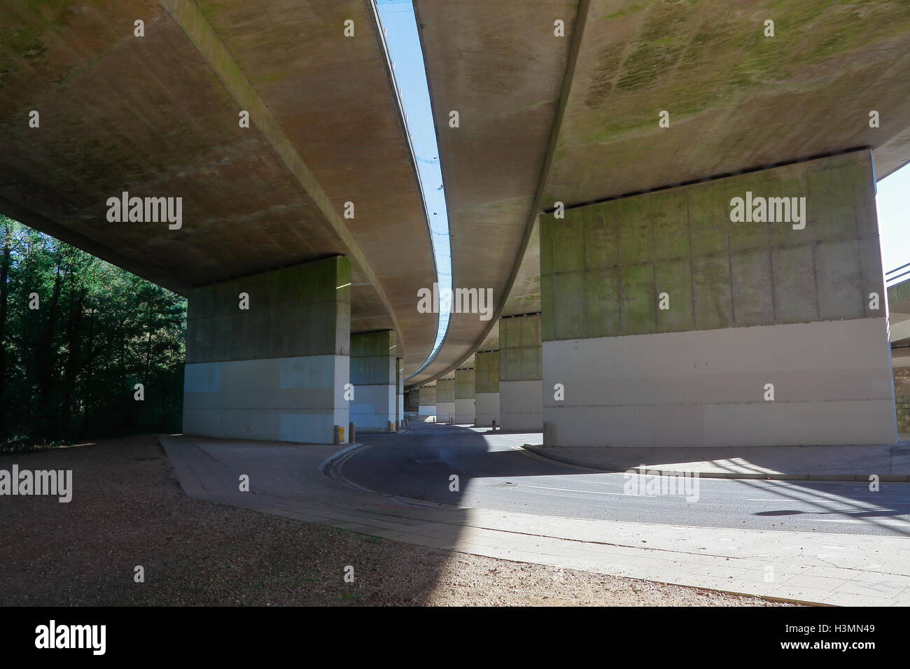 Looking up under the arches of a huge curved concrete flyover with a space between dual carriageways. - Stock Image