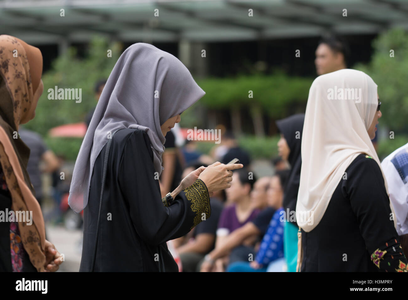 Muslim women wearing Hijab & using a mobile phone near to the Petronas Twin Towers,Kuala Lumpur,Malaysia - Stock Image