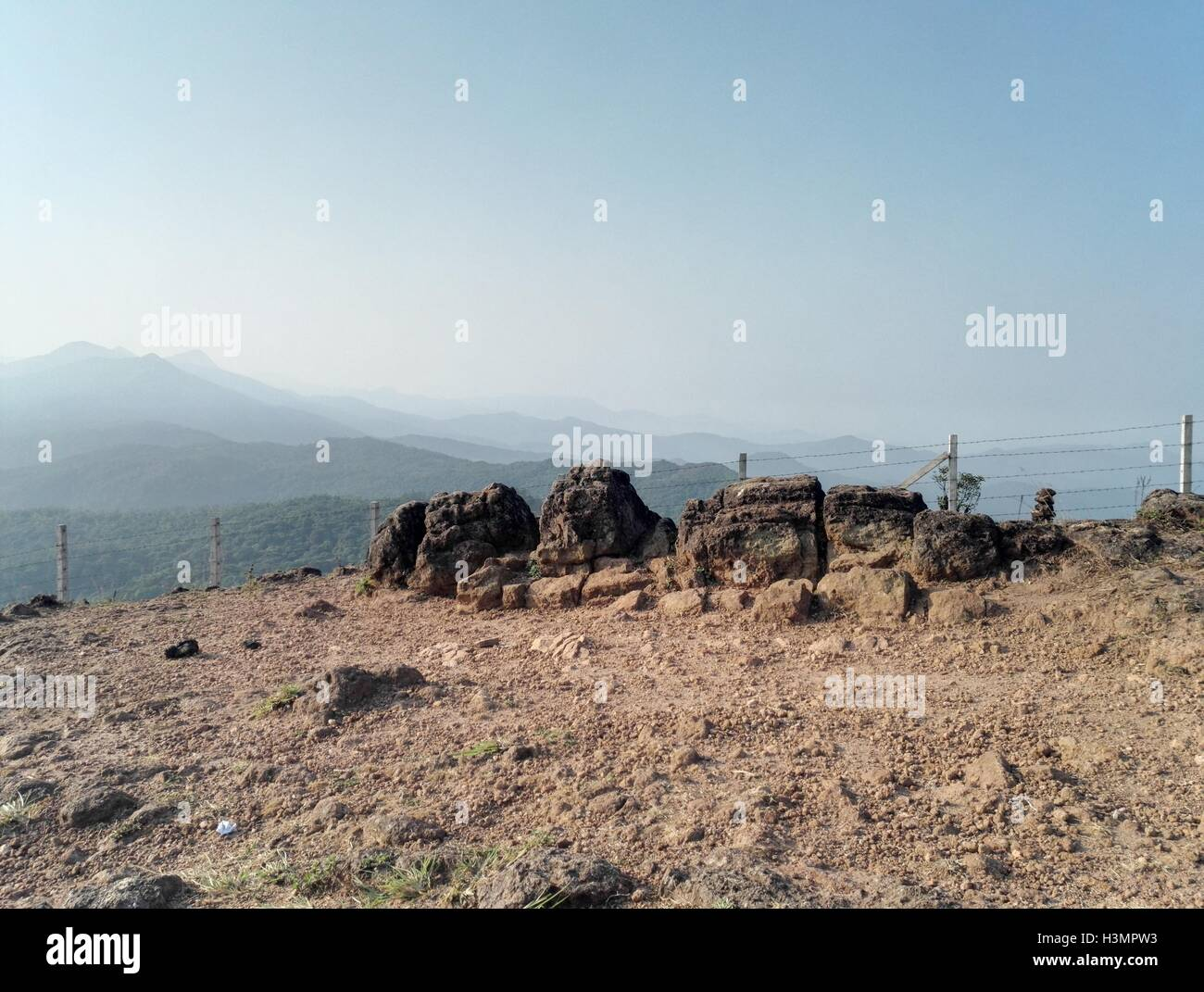 A barbed wire fence on a hill top - Stock Image