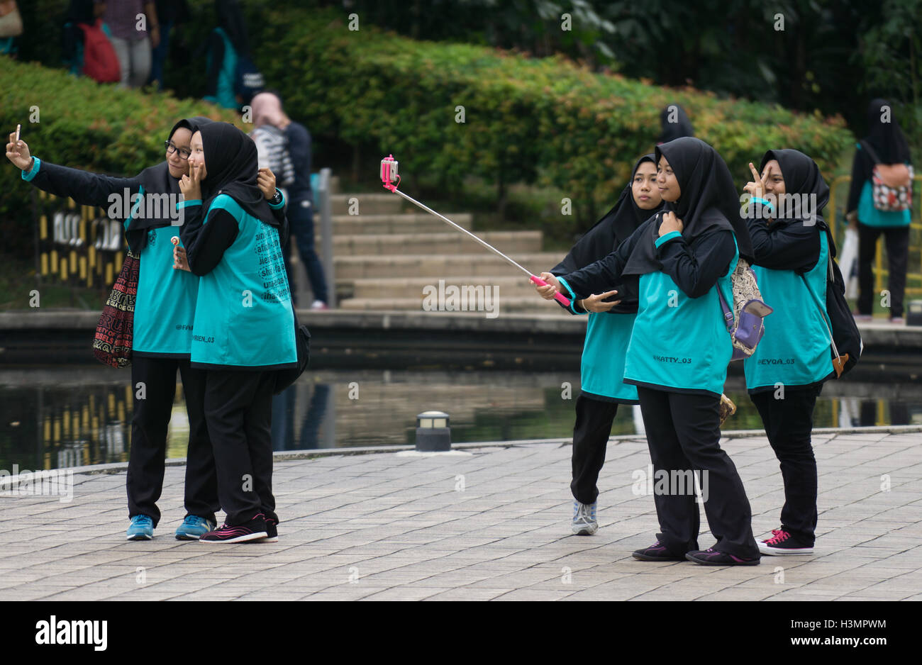 A group of Muslim girls wearing Hijabs taking Selfies on a mobile phone near to the Petronas Twin Towers,Kuala Lumpur,Malaysia - Stock Image