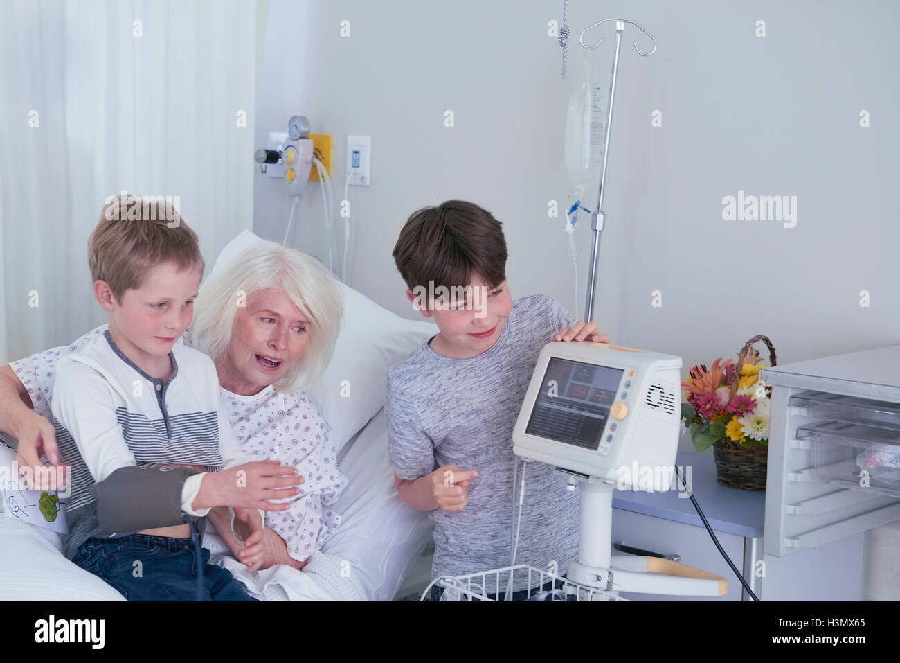Senior female patient in hospital bed with grandsons playing with blood pressure machine - Stock Image