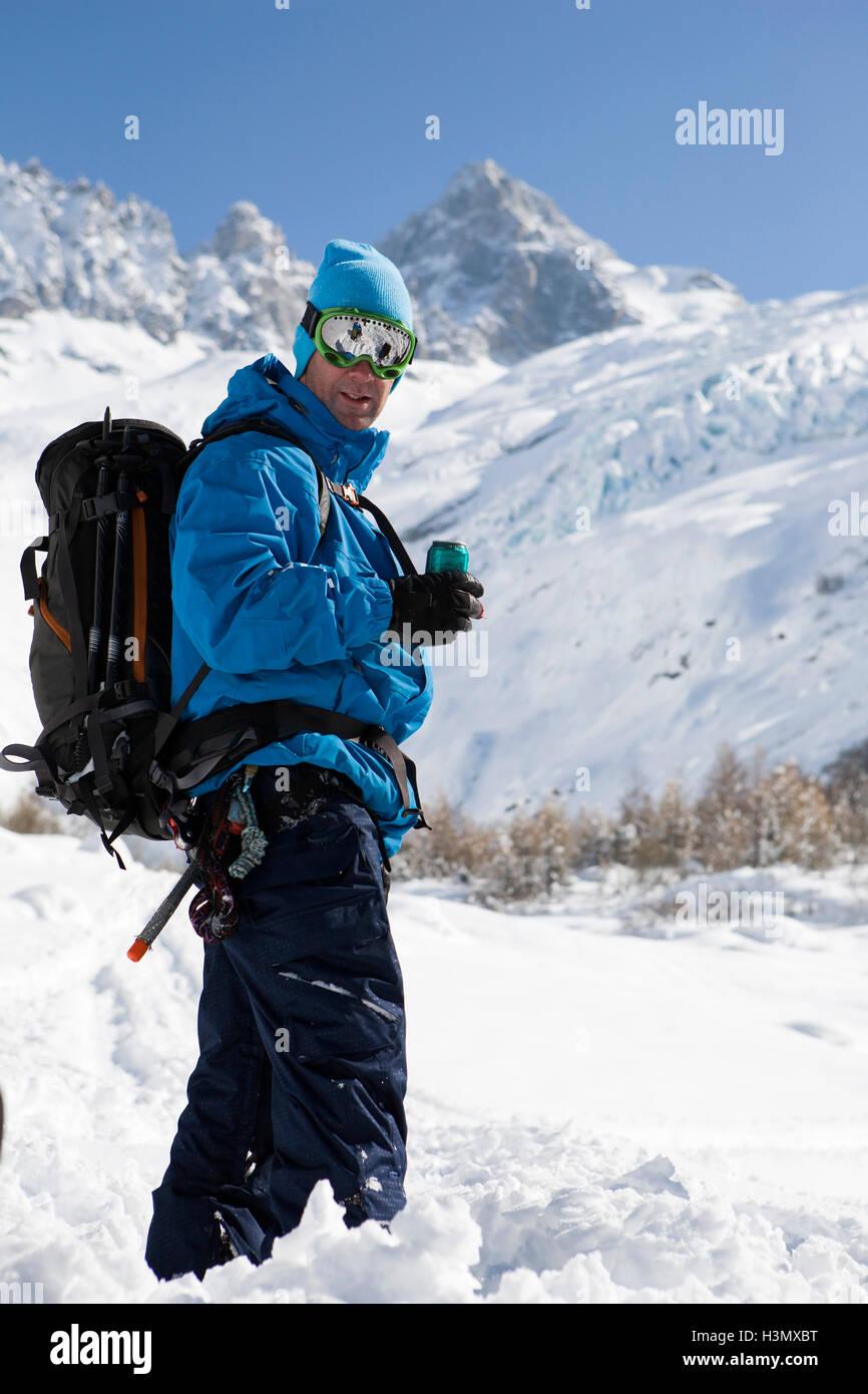 Portrait of male snowboarder wearing ski goggles in deep snow, Trient, Swiss Alps, Switzerland - Stock Image