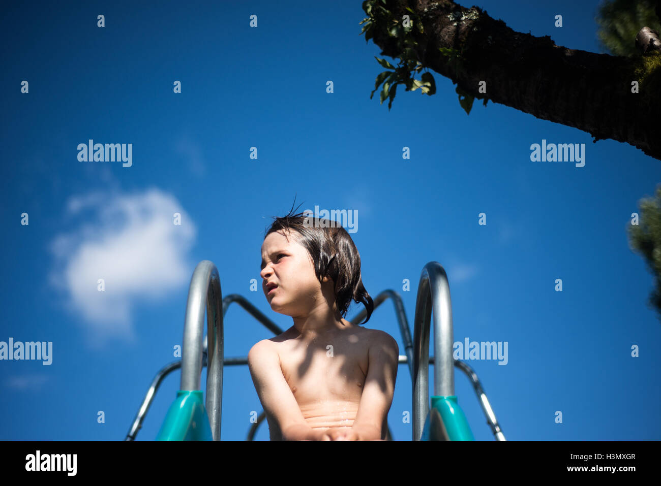 Boy on top of playground slide looking away - Stock Image