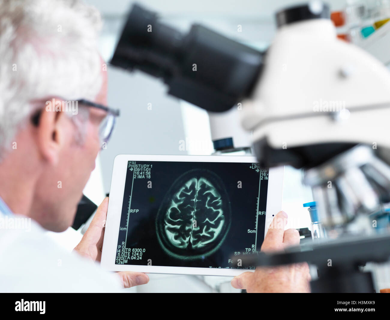 Doctor viewing a MRI brain scan on digital tablet in a laboratory - Stock Image