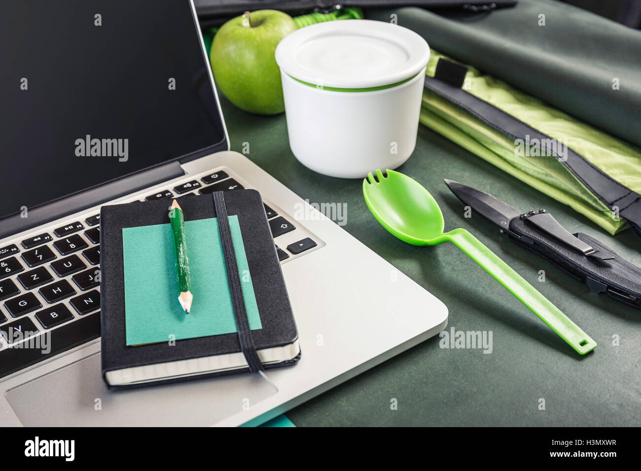 Laptop, notebook and pocket knife on table - Stock Image