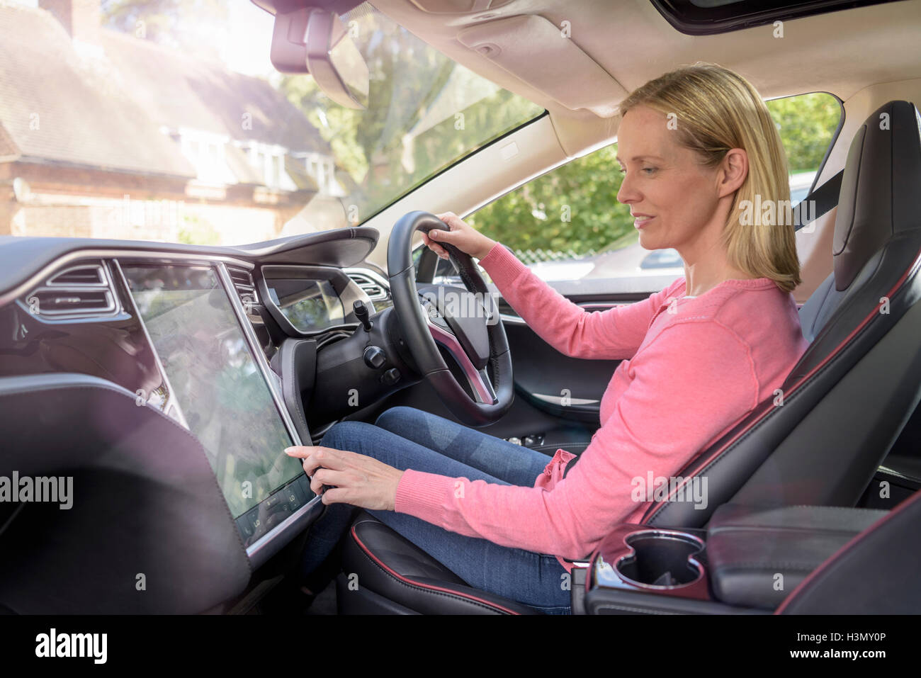 Woman using satellite navigation system in electric car - Stock Image