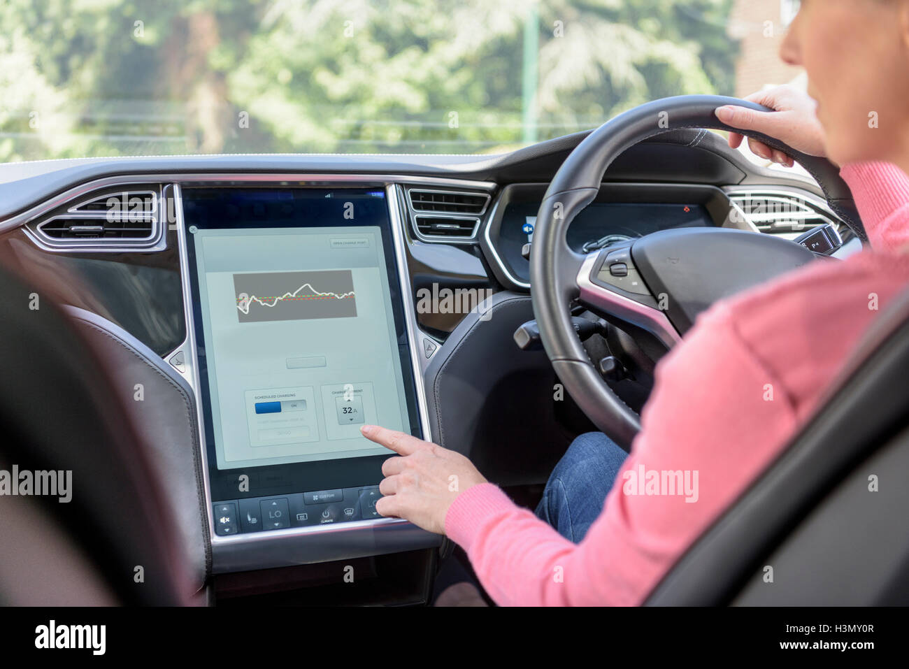 Woman using graphical display in electric car - Stock Image