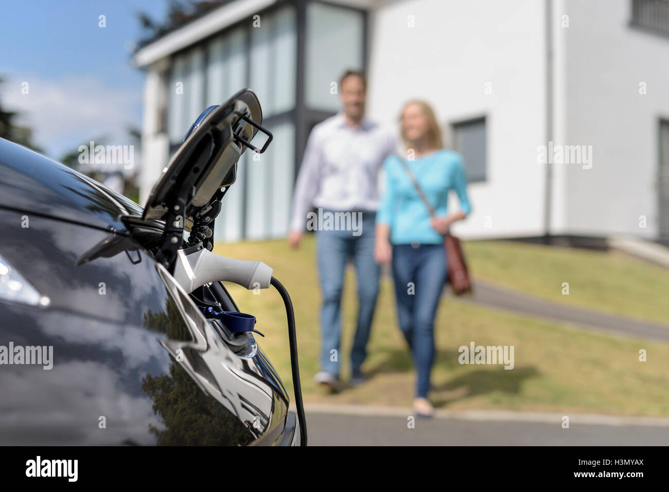 Man and woman walking towards electric car being charged - Stock Image