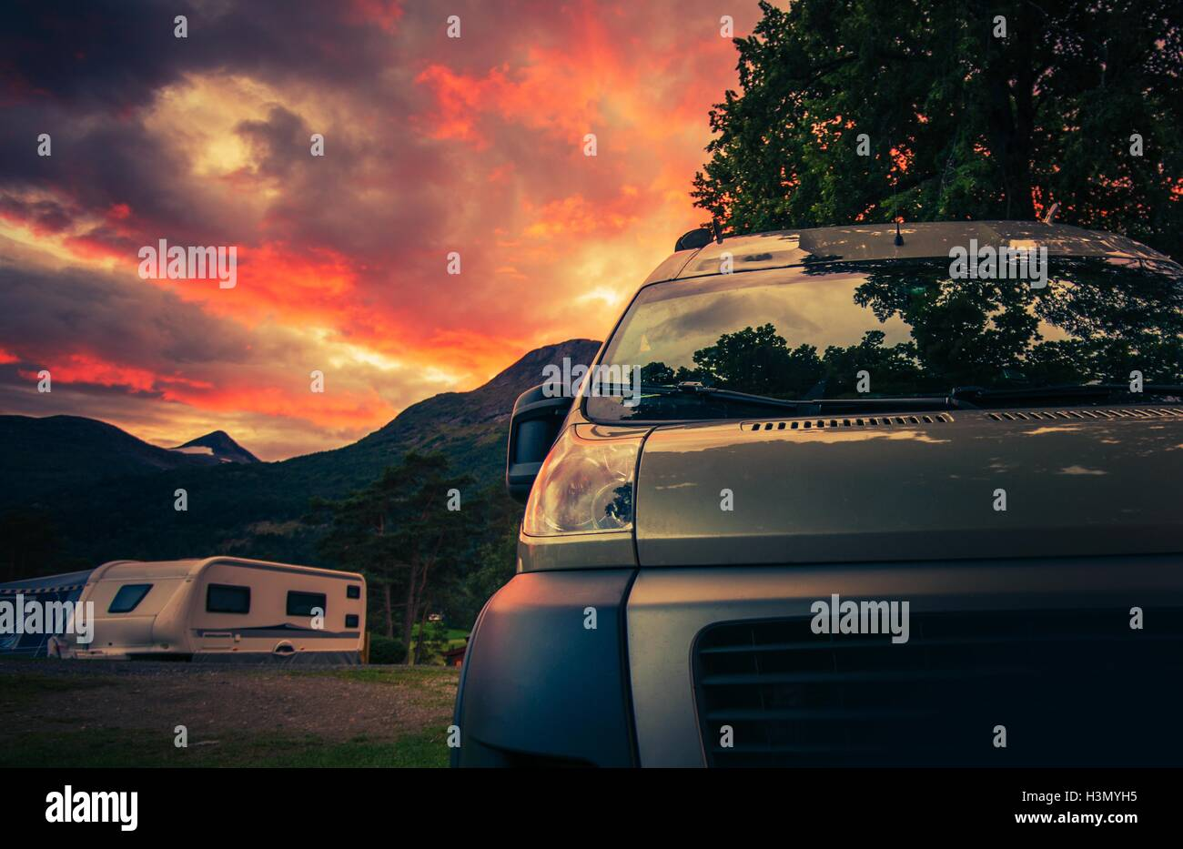 Scenic RV Park Camping During Beautiful Summer Sunset. Motorhome and Travel Trailers in the Background. - Stock Image