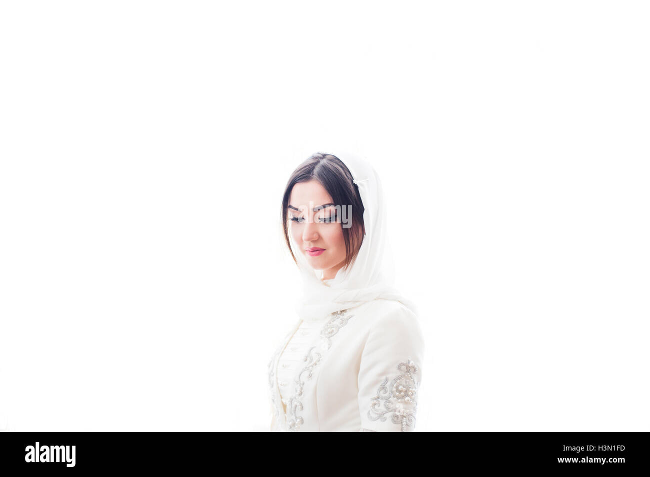 muslim girl in a white wedding hijab closed her eyes - Stock Image