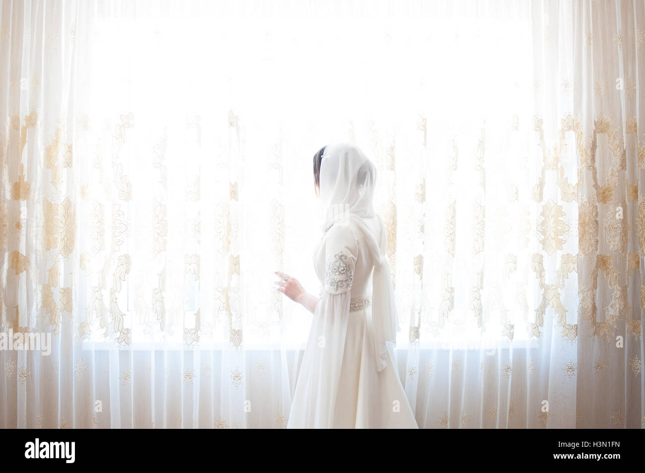 muslim woman in a white headscarf looking out the window - Stock Image