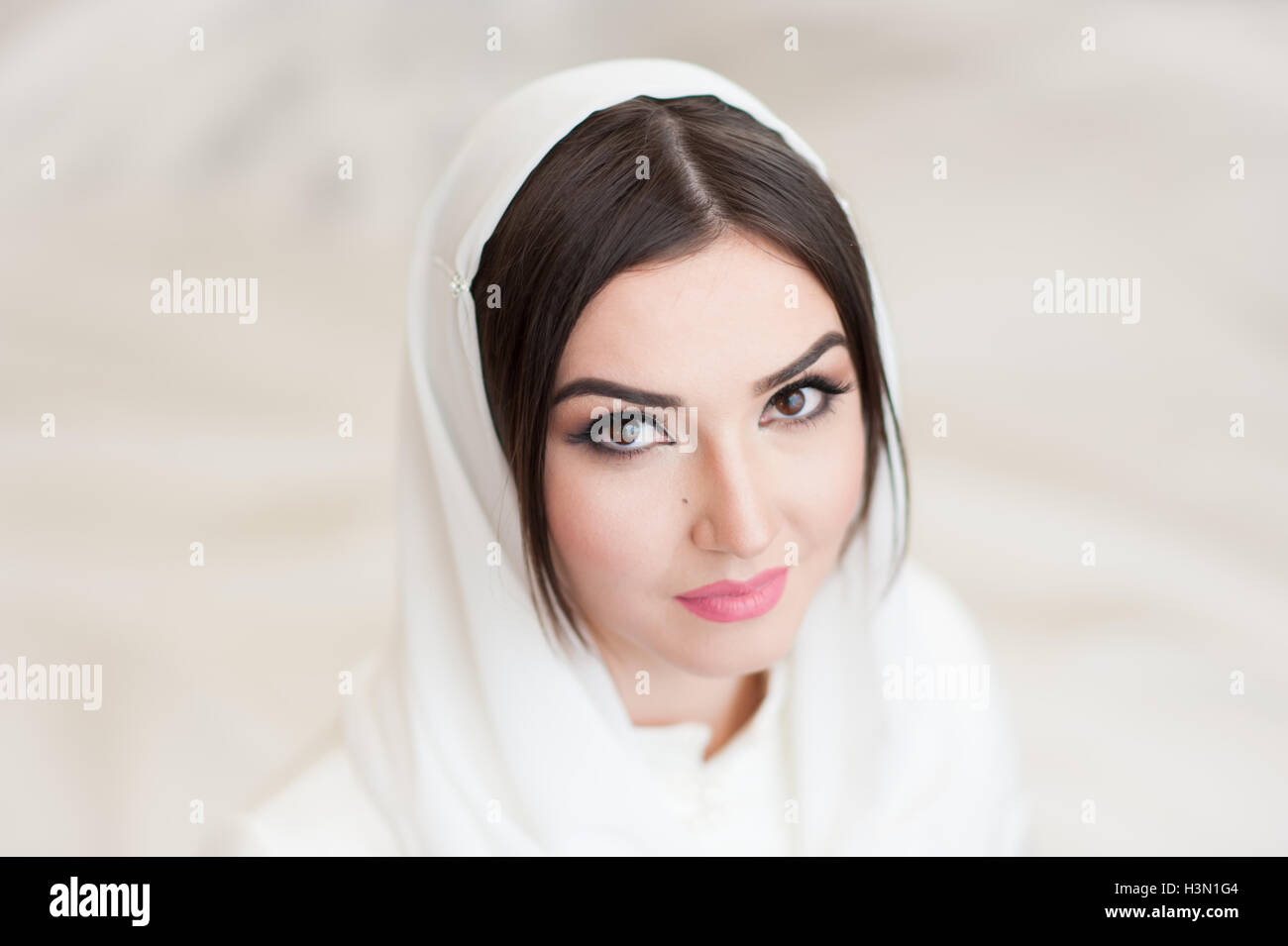 portrait of beautiful girl in white headscarf - Stock Image