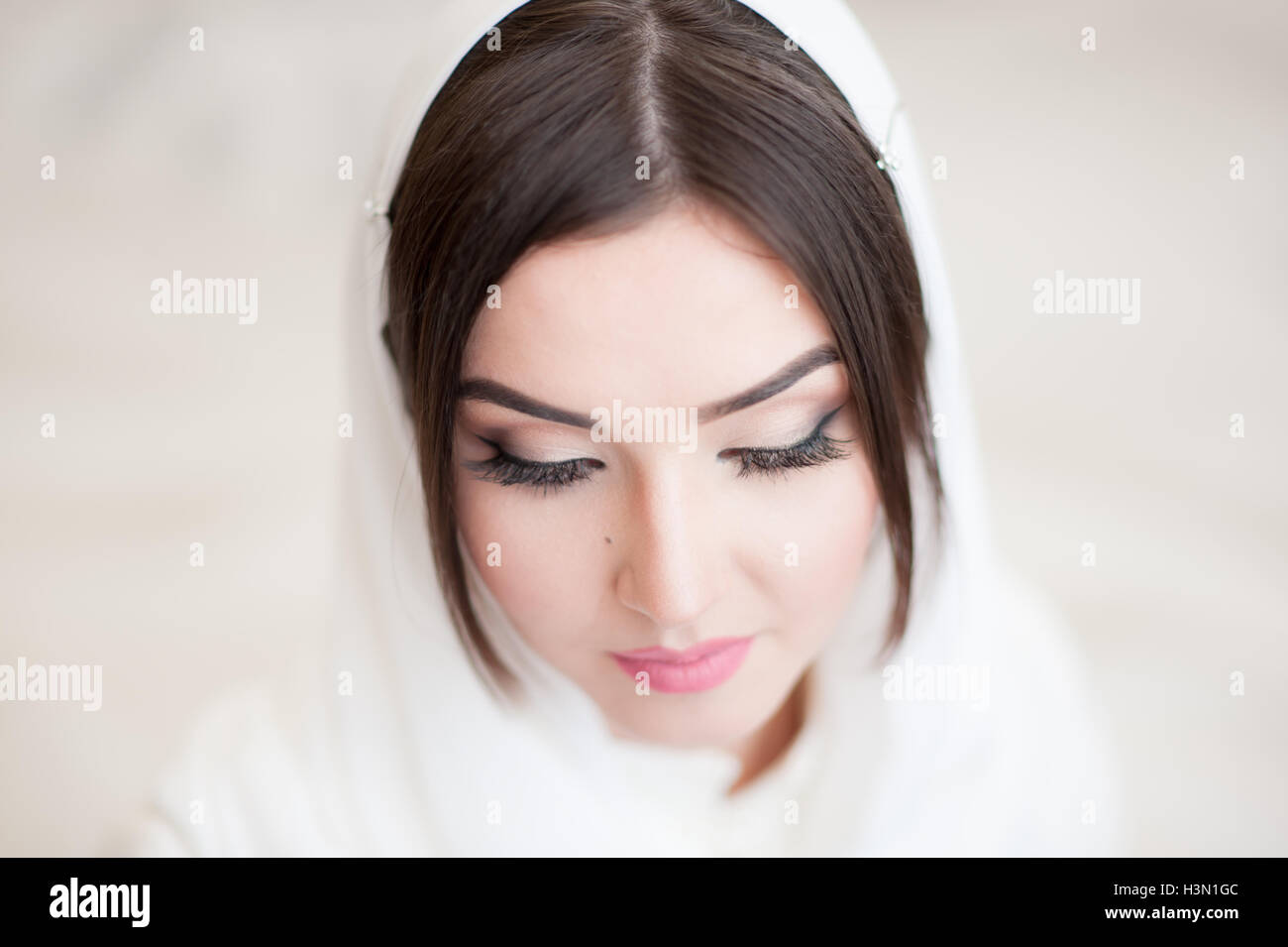 beautiful young woman in a white hijab closed her eyes - Stock Image