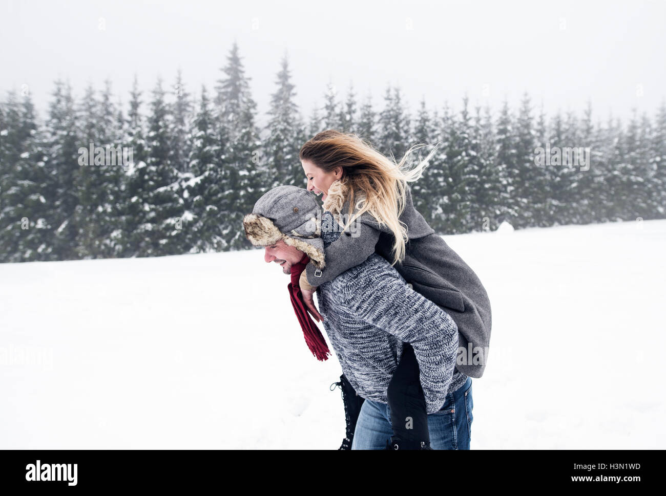 Couple in love, man giving woman piggyback. Winter nature. Stock Photo