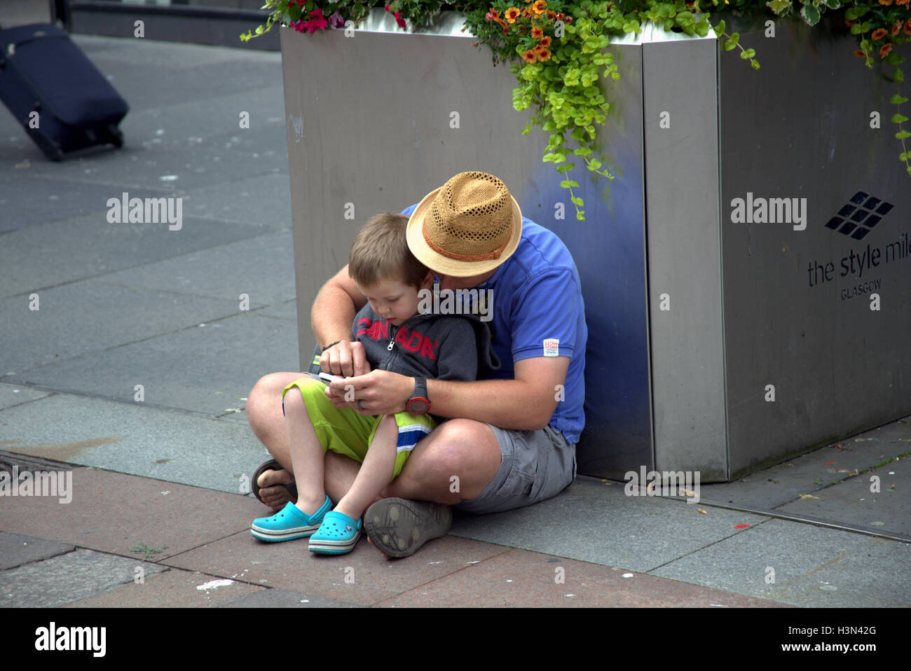 Glasgow street scenes father and son use mobile phone together while sitting on ground Stock Photo