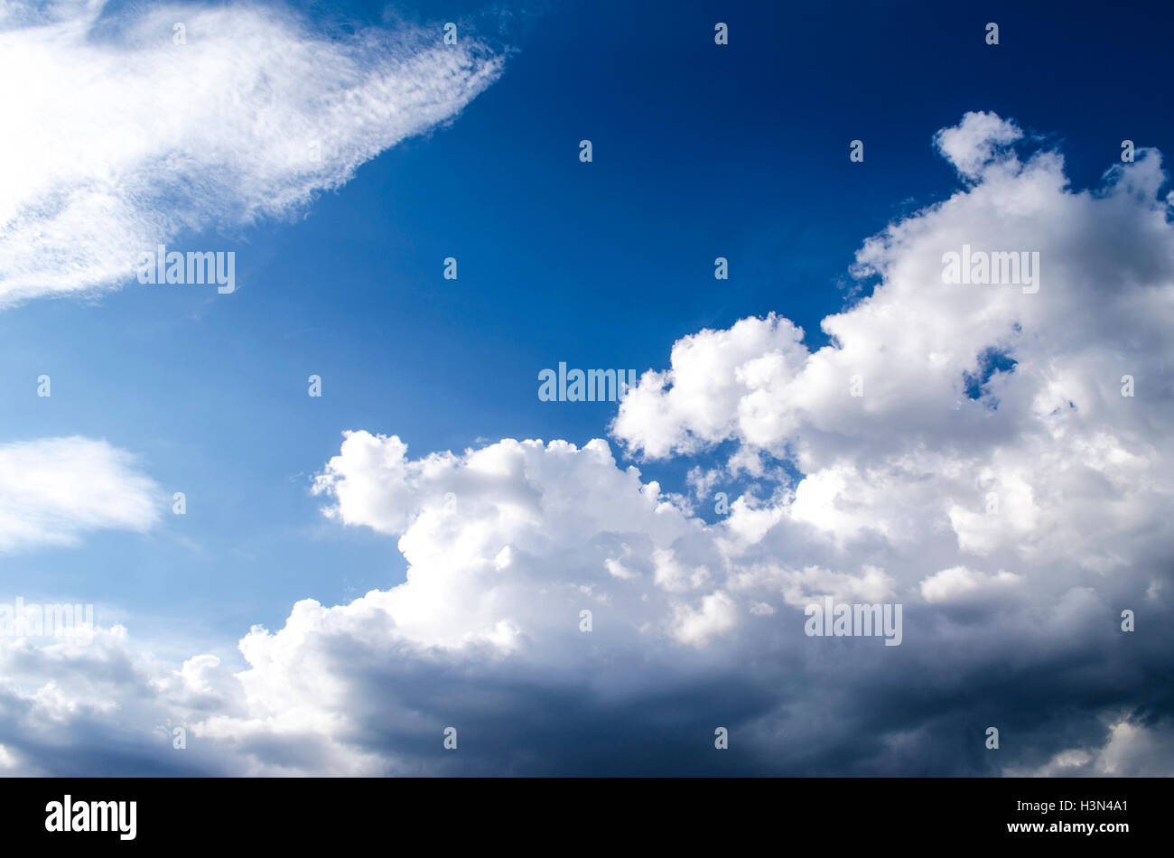 Dark rainy clouds covering the sunny calm sky - Stock Image
