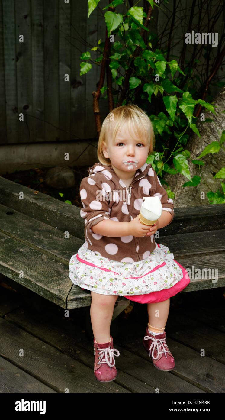 A little girl (2 yr old) eating an ice cream