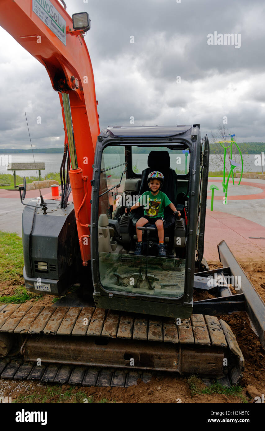 A young boy (4 yrs old) sitting a JCB (excavator) cabin pretending to operate it. - Stock Image