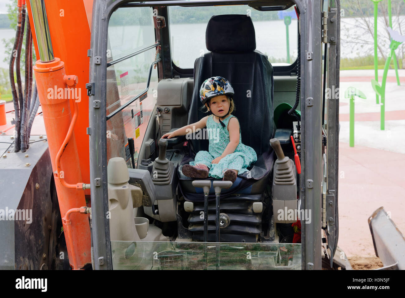 A young girl (2 yrs old) sitting a JCB (excavator) cabin pretending to operate it. - Stock Image