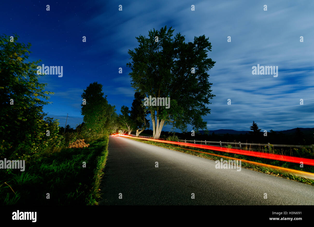 Car headlights and tail lights moving down a country lane at night - Stock Image