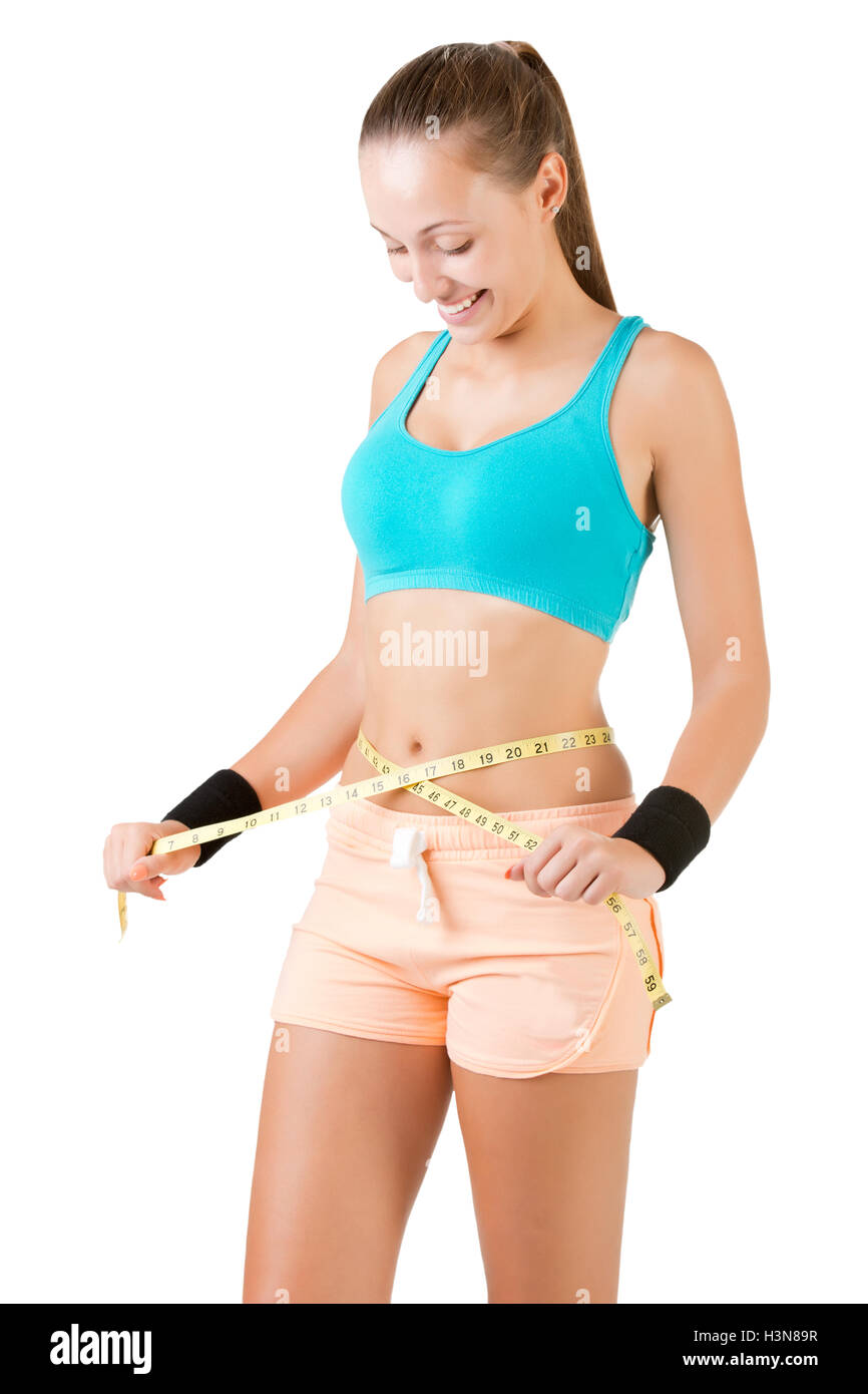 Woman measuring her waist with a yellow measuring tape, isolated in white - Stock Image
