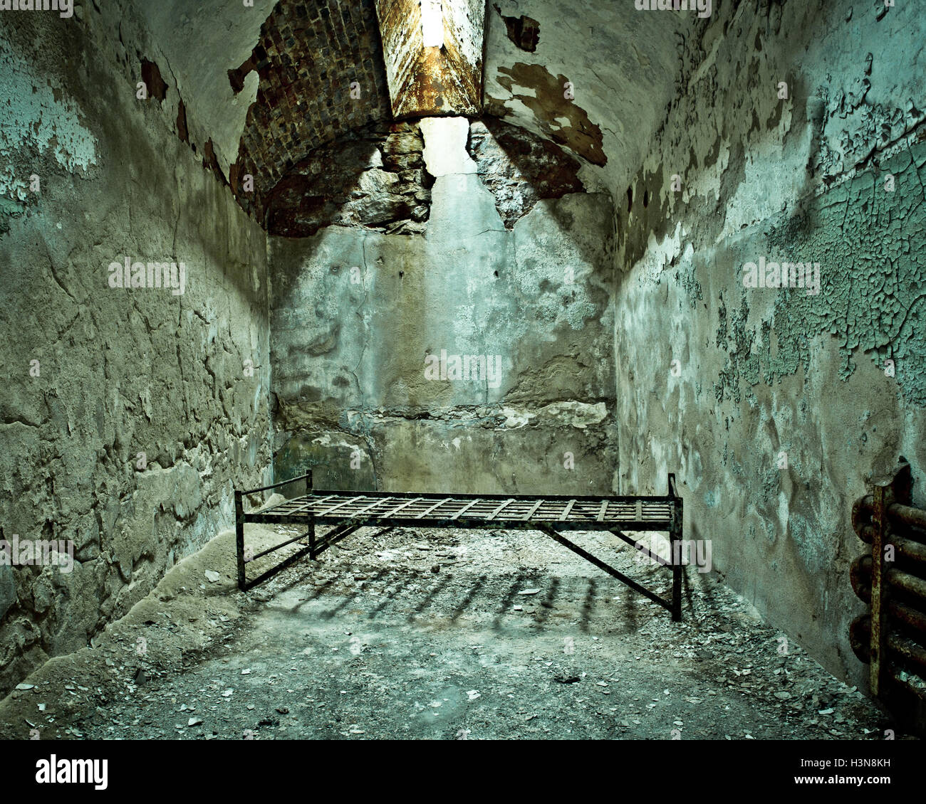 Crumbling abandoned prison cell with cot - Stock Image