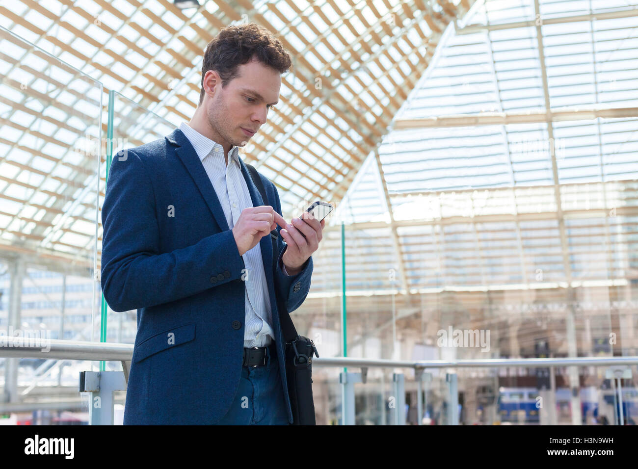 Businessman writing a message on smartphone, train station waiting lounge in background - Stock Image