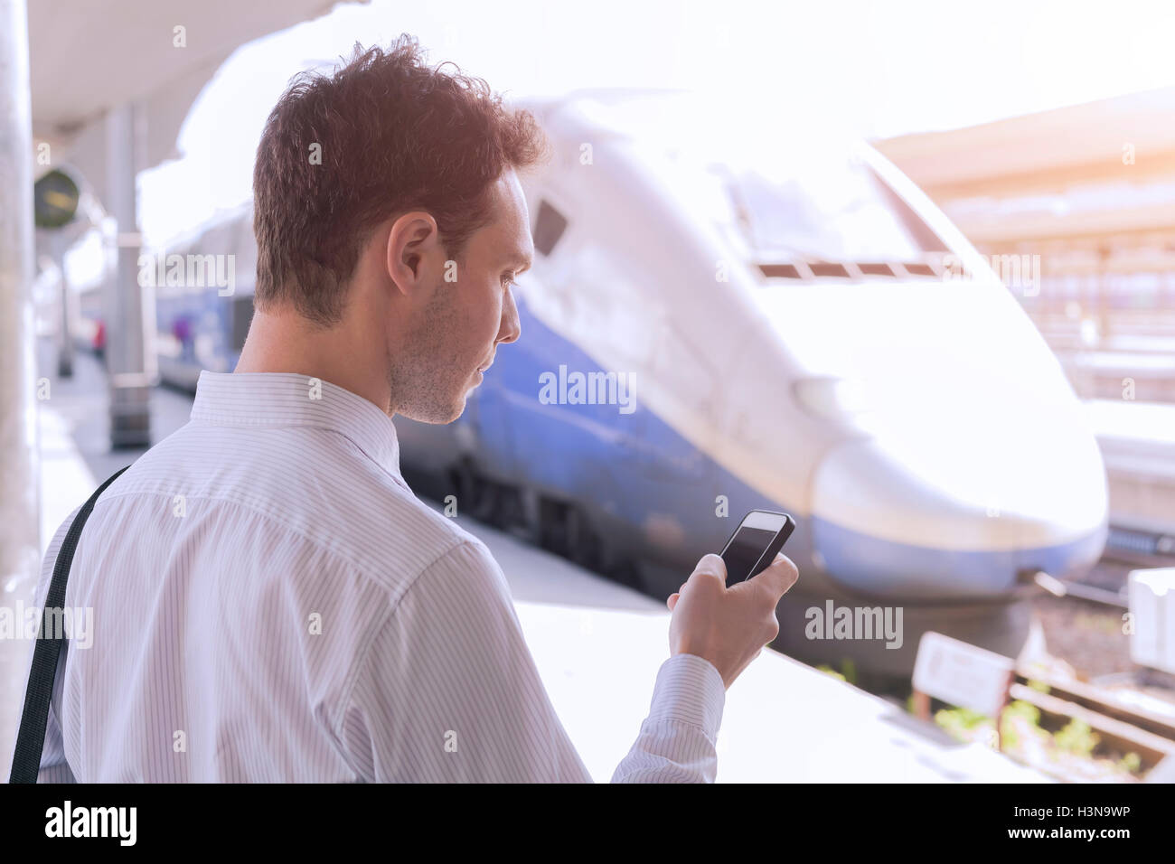 Young adult male using app on smartphone during business travel with train in background - Stock Image
