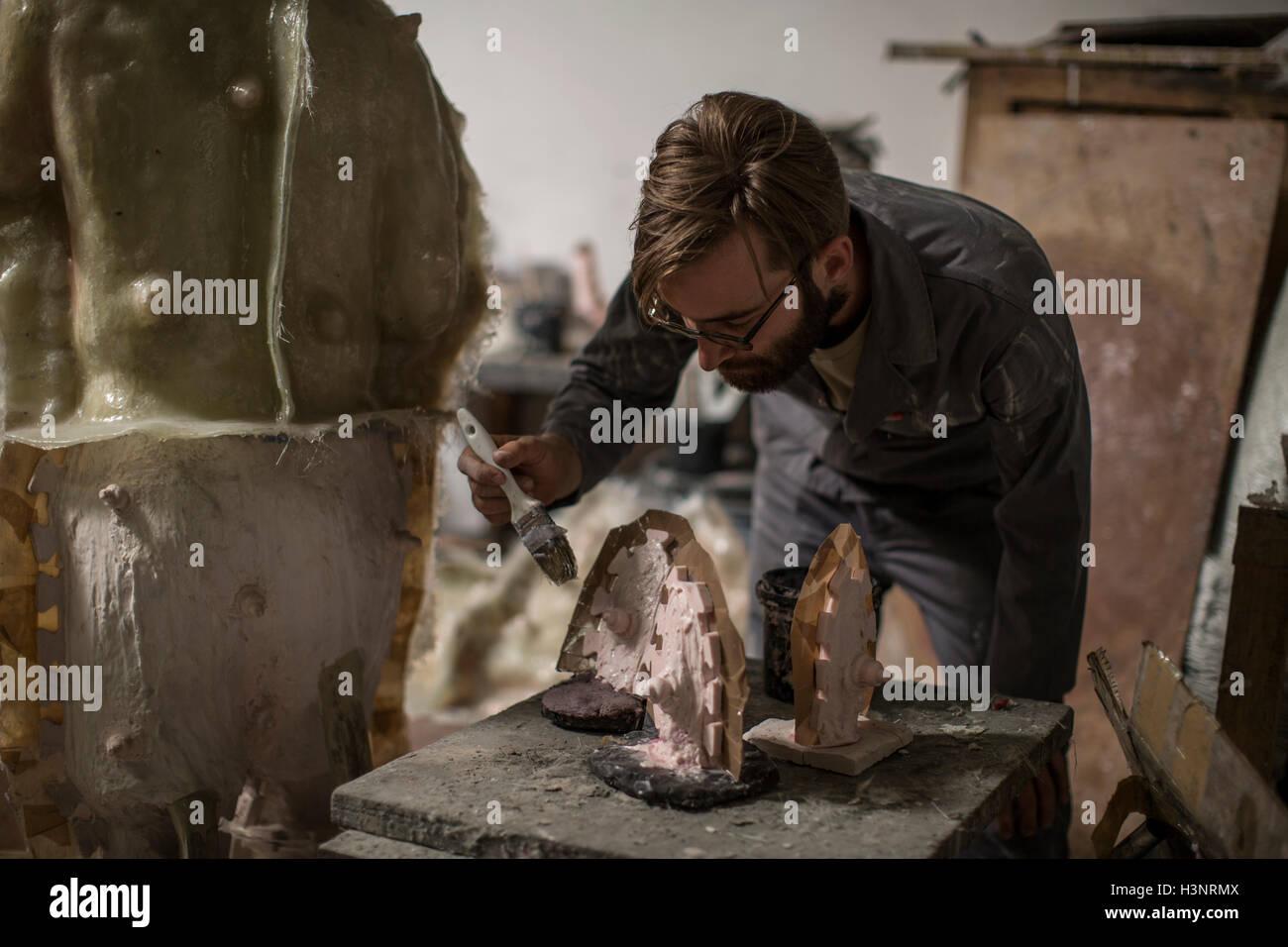 Sculptor in artists' studio creating sculpture - Stock Image