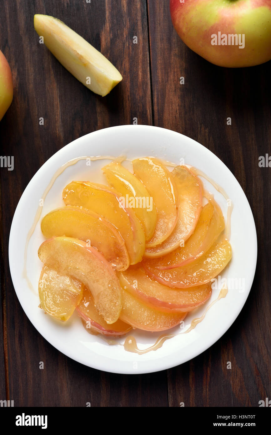 Caramelized apple slices on plate, top view - Stock Image
