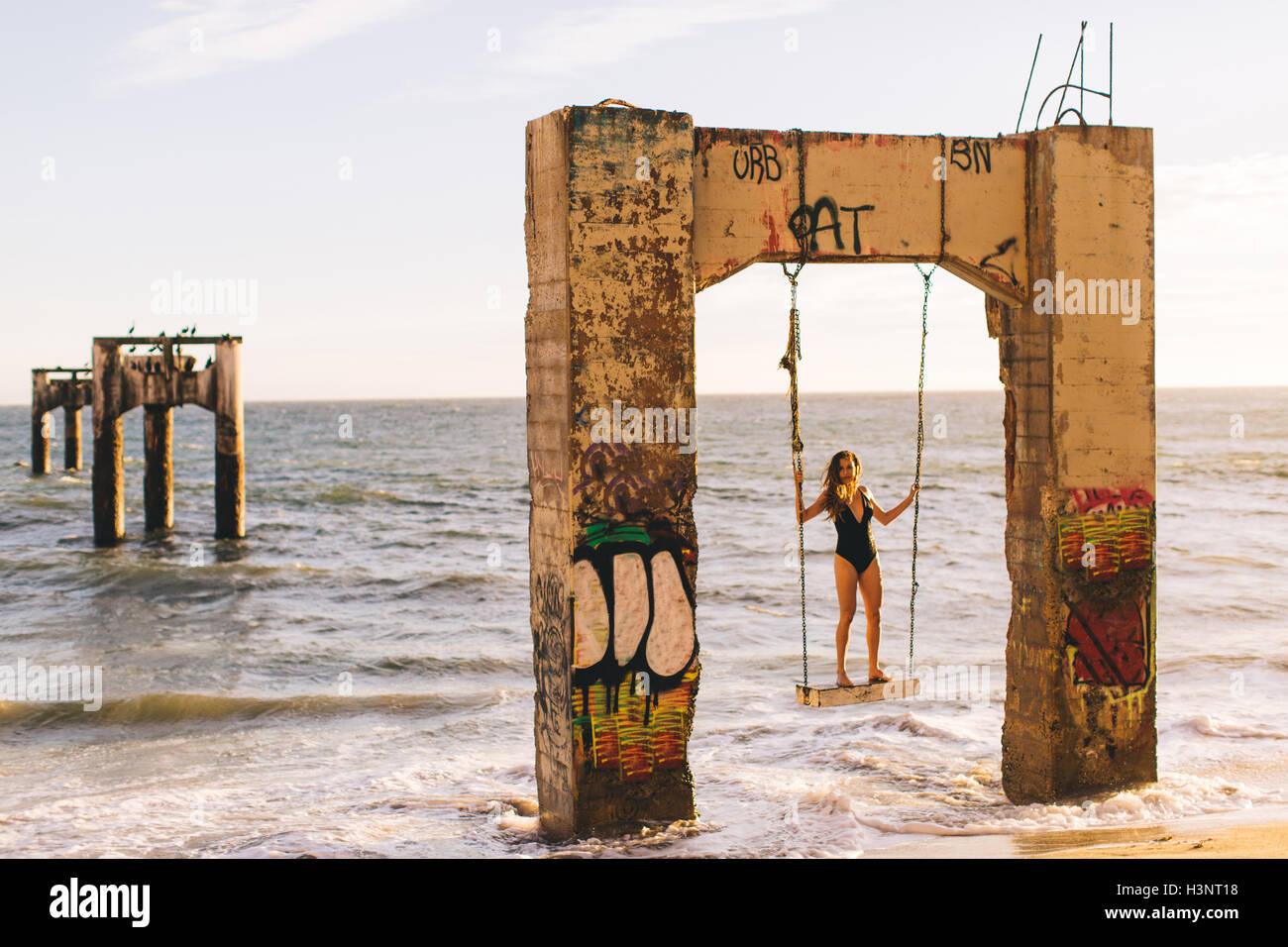 Woman standing on swing, Old Davenport Pier, Santa Cruz, California, USA - Stock Image