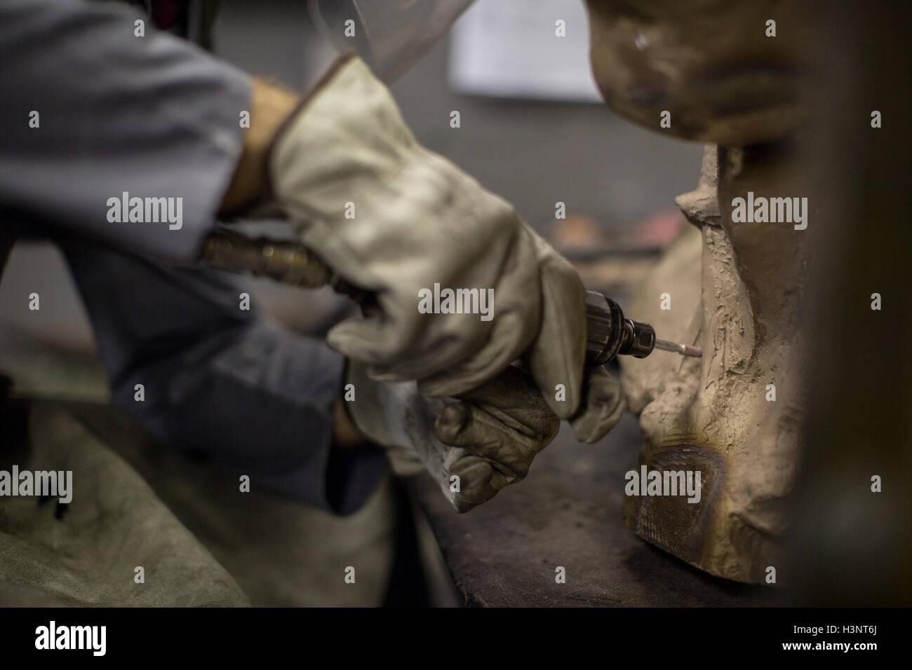 Sculptor in artists' studio creating sculpture using hand tool - Stock Image