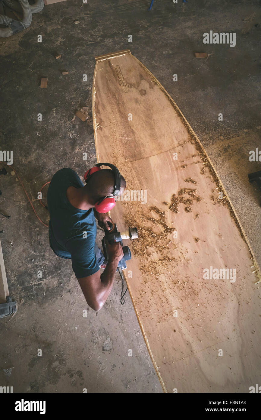Craftsman making paddleboard in workshop, overhead view - Stock Image